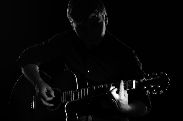 Man with guitar in darkness