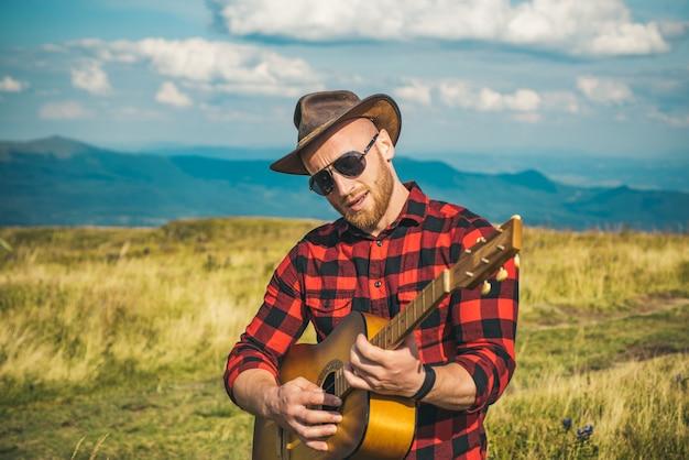 自然のヒップスターにギターを持っている男はキャンプの休日にギターを弾く
