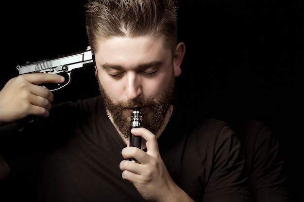 A man with a gun attached to his temple smokes an electronic cigarette, the concept of instant or slow death,