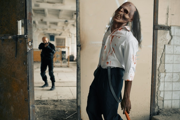 Человек с перестрелкой сражается с зомби-нежитью, кошмар на заброшенной фабрике. ужас в городе, жуткие ползания, апокалипсис судного дня, кровавый злой монстр