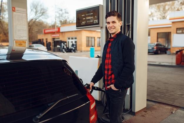 Человек с пушкой заправляет автомобиль на азс, заправка топливом. заправка бензином, бензином или дизельным топливом