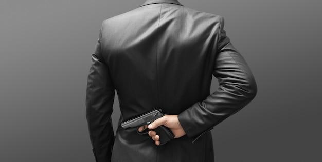 Man with a gun behind his back.