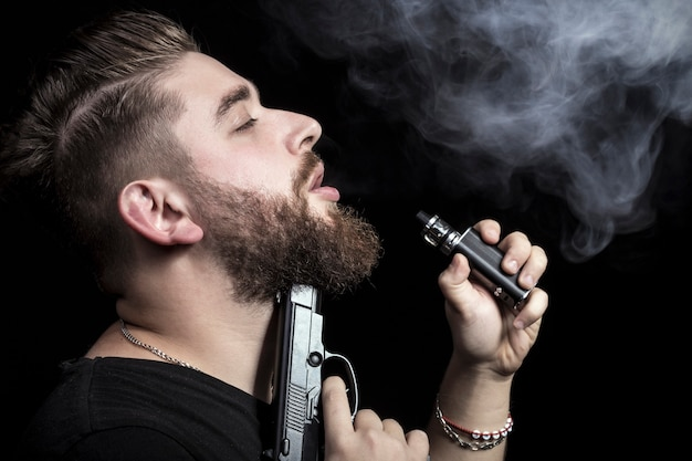 A man with a gun to his chin smokes an electronic cigarette, the concept of instant or slow death,
