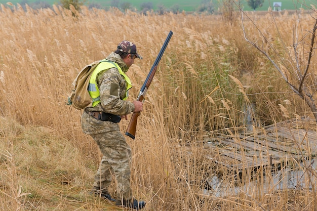 A man with a gun in his hands and an green vest on a pheasant hunt in a wooded area
