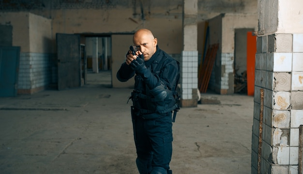 廃工場で銃を持った男。街の恐怖、不気味な這う攻撃、終末の黙示録、怖い場所