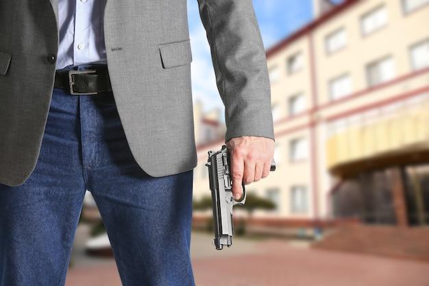 屋外の学校の近くで銃を持った男