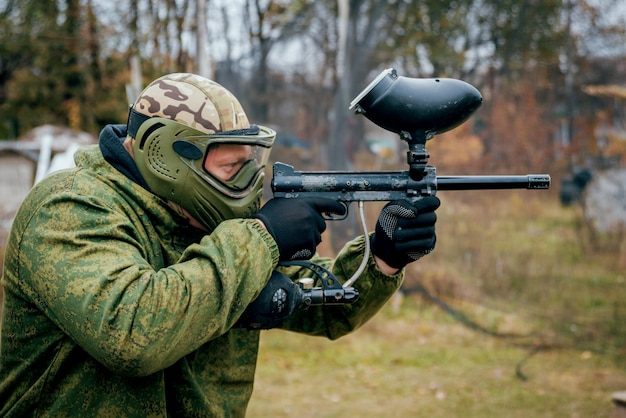 Man with gun playing at paintball. outdoors