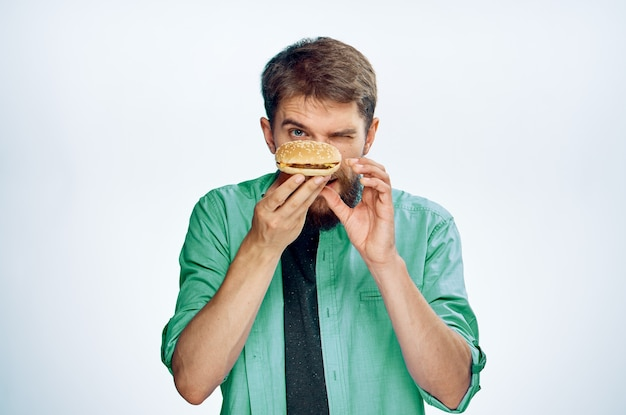 Мужчина с гамбургером руки еда зеленая рубашка галстук светлый фон