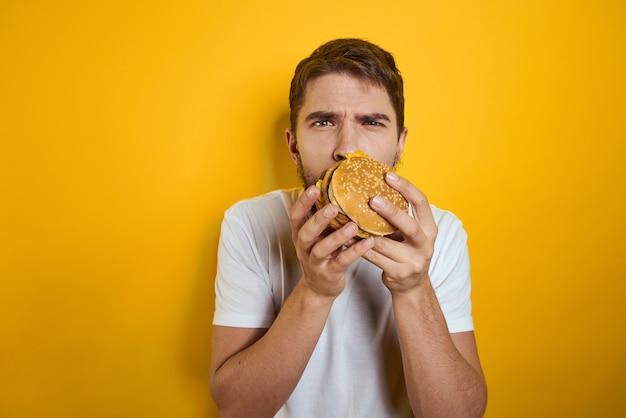 ファーストフードダイエット食品白いtシャツのクローズアップ黄色の背景の手にハンバーガーを持つ男
