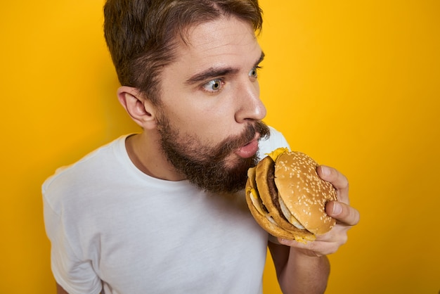 Человек с гамбургером в руках фаст-фуд диетическая еда белая футболка крупным планом