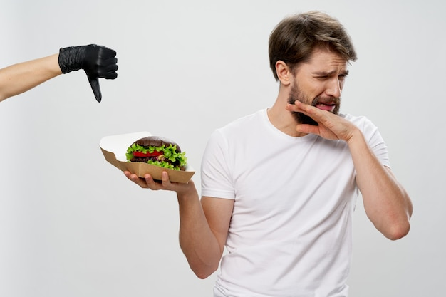 Man with hamburger in white tshirt disgust diet calorie