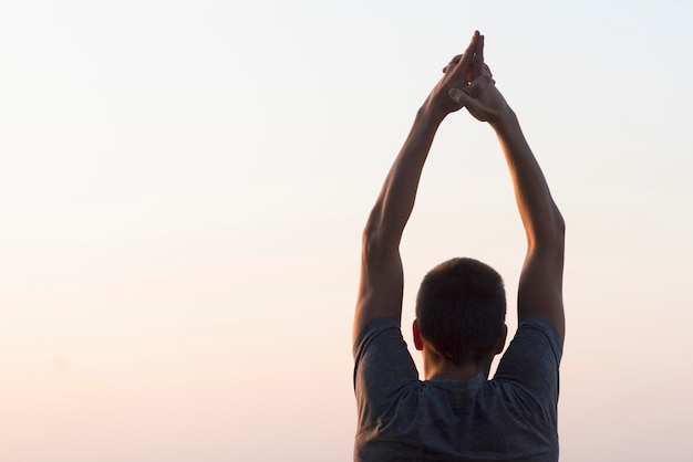 Человек с руками в воздухе, глядя на небо