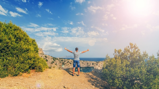 Man with hands raised outdoors in summer on the background of the sea on the top of the mountains