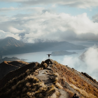 湖の素晴らしい景色を楽しむ山の頂上に立って両手を大きく開いた男