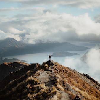 Uomo con le mani spalancate in piedi in cima a una montagna che si gode l'incredibile vista di un lago