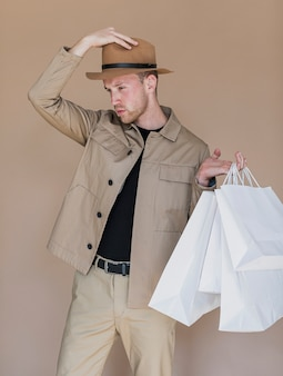 Uomo con cappello sulla testa e borse della spesa