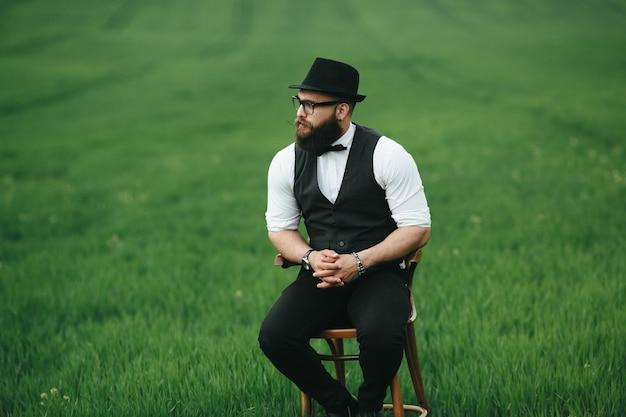 Человек в шляпе, сидя на стуле, на открытом воздухе