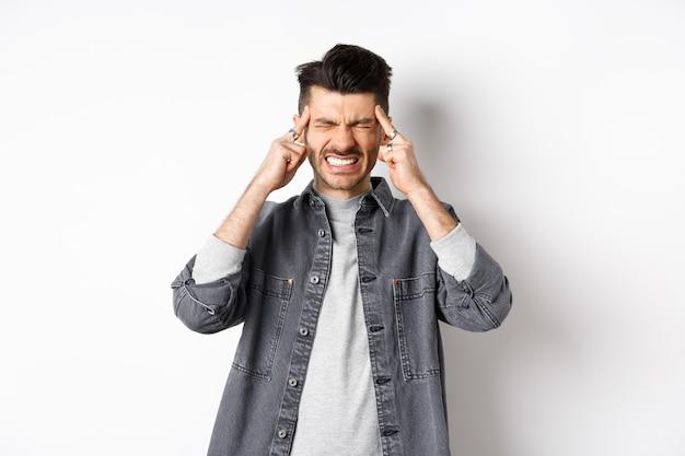 Человек с головной болью, гримасничающий и стиснув зубы от болезненной мигрени, касающийся головных висков, страдающий мигренью, нуждается в обезболивающих, стоя на белом фоне.