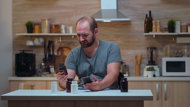 台所に座っている薬瓶を保持している頭痛を持つ男。めまい症状で疲れ果てた片頭痛、うつ病、病気、不安感に苦しんでいるストレスのたまった不幸な心配している人。