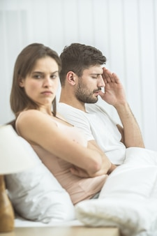 The man with a headache sit near woman on the bed