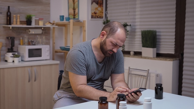 Man with headache using smartphone to search informations. stressed tired unhappy worried person suffering of migraine, depression, disease and anxiety feeling exhausted with dizziness symptoms.