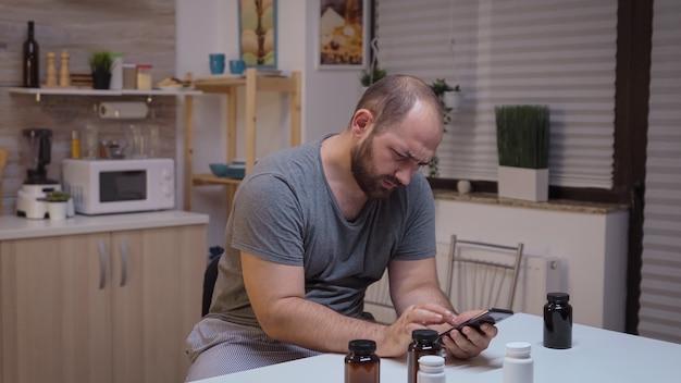 情報を検索するためにスマートフォンを使用して頭痛のある人。めまい症状で疲れ果てた片頭痛、うつ病、病気、不安感に苦しんでいるストレスのたまった不幸な心配している人。