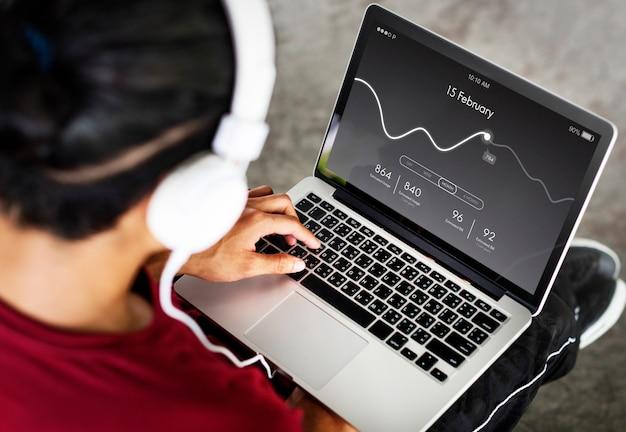헤드폰을 든 남자는 온라인 통계를 분석합니다.