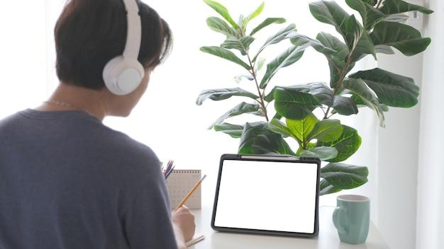 모의 템플릿을 위한 작업 테이블에 검은 화면이 있는 헤드폰과 디지털 태블릿을 가진 남자