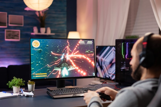 ヘッドフォンとジョイスティックのストリーミングスペースを持つ男は、ゲームのホームスタジオでビデオゲームを撮影します。強力なコンピューターで遊ぶゲームの競争のためにオンラインで他のプレーヤーと話しているプロのプレーヤーの男