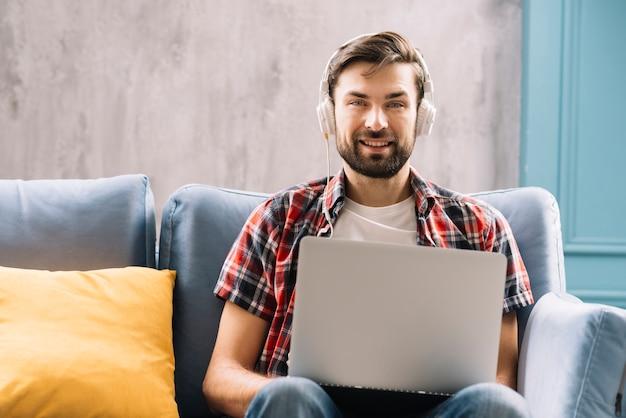 Человек с наушниками и ноутбуком, глядя на камеру