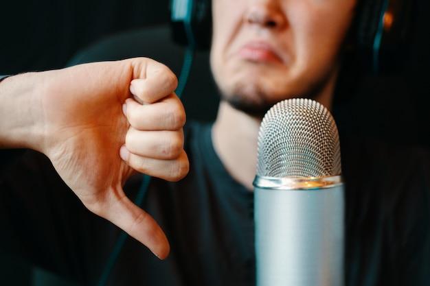 ポッドキャストスタジオでヘッドフォンとマイクを持った男。ジェスチャーが嫌い。ヴィンテージマイク