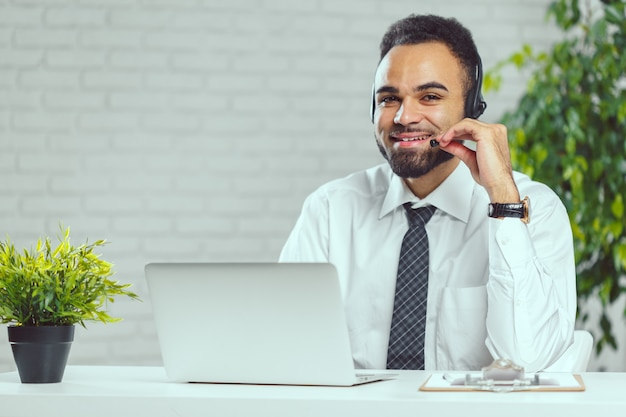 Man with headphones  call center operator speaking with client
