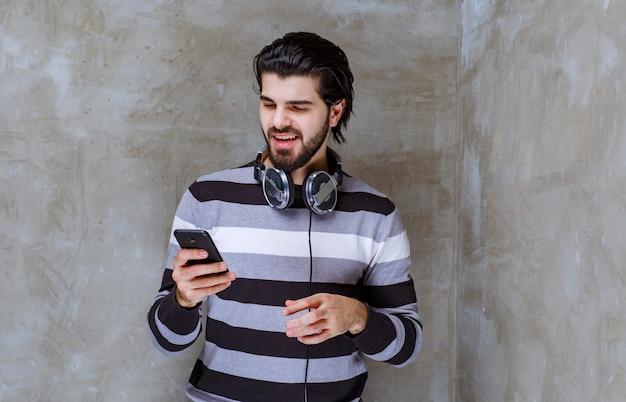 Uomo con le cuffie che controlla i suoi messaggi o la sua playlist musicale con energia positiva