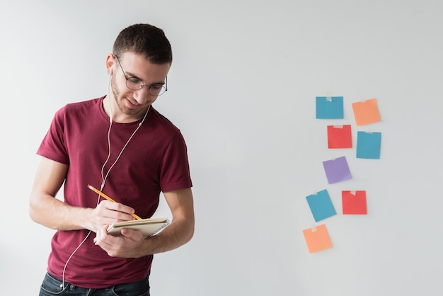 Man with headphones and glasses writing