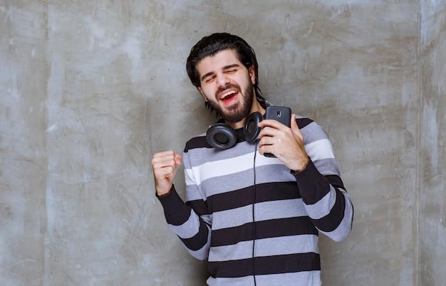 Человек с наушниками держит черный телефон и показывает знак удовлетворения