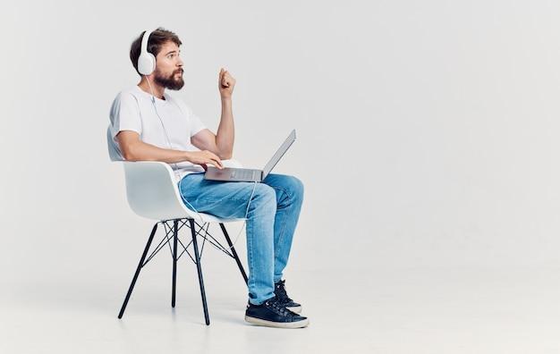 Человек с наушниками перед ноутбуком, сидя на стуле в офисе коммуникационных технологий