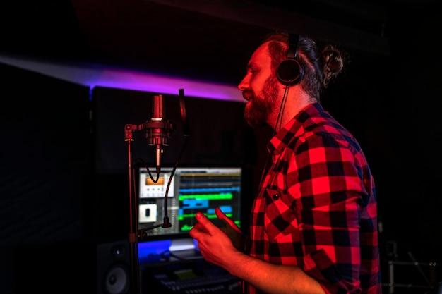 헤드폰을 든 남자가 라디오에서 마이크에 노래를 부르며 그의 새로운 노래를 방송합니다.