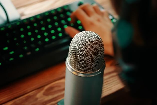 ヘッドフォンを持っている人がキーボードで入力し、レトロな古いマイクのラジオ番組やオーディオポッドキャストの概念でポッドキャスティング