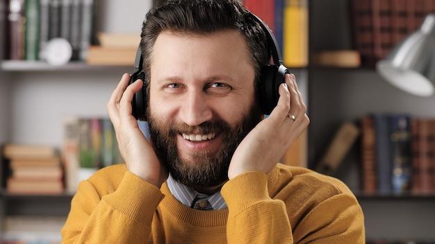 Человек с наушниками смеется. позитивный бородатый учитель-мужчина или бизнесмен берет наушники руками, глядя на кого-то и смеясь. средний выстрел