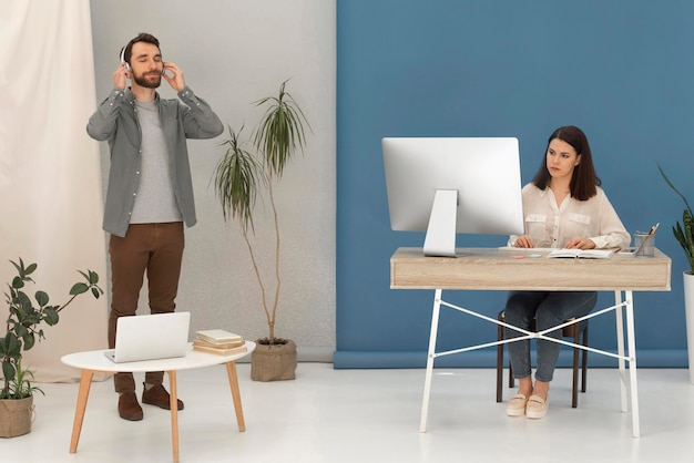 Man with headphones listening music and stressed woman working on laptop