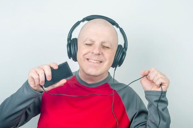 디지털 휴대용 플레이어를 통해 음악을 듣는 헤드폰을 가진 남자