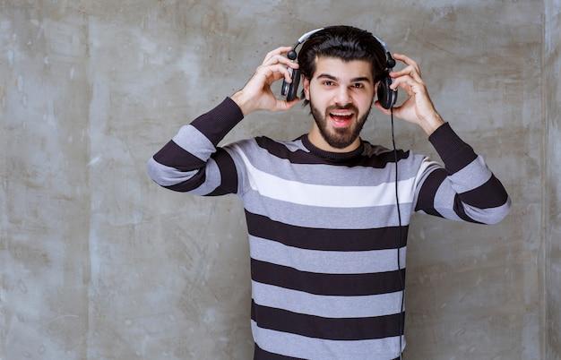 音楽を聴いて笑っているヘッドフォンを持つ男