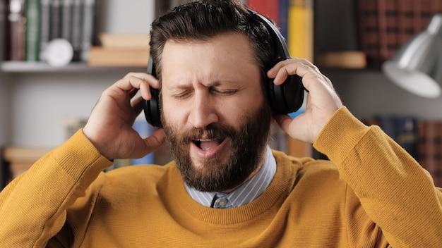 Мужчина в наушниках слушает музыку и поет. позитивный бородатый мужчина в черных беспроводных наушниках держит голову руками и поет песню, наслаждаясь музыкой. средний выстрел