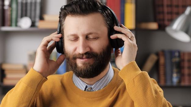 Человек в наушниках слушает музыку. позитивный бородатый мужчина в черных беспроводных наушниках держит голову руками и наслаждается музыкой. средний выстрел