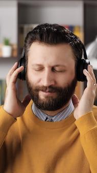 Человек в наушниках слушает музыку. вертикальный вид позитивного бородатого мужчины в черных беспроводных наушниках держит голову руками и наслаждается музыкой. средний выстрел