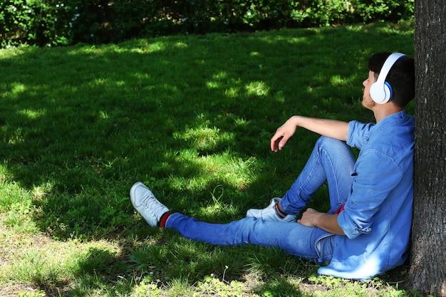 공원에있는 나무 아래에서 쉬고 헤드폰을 가진 남자