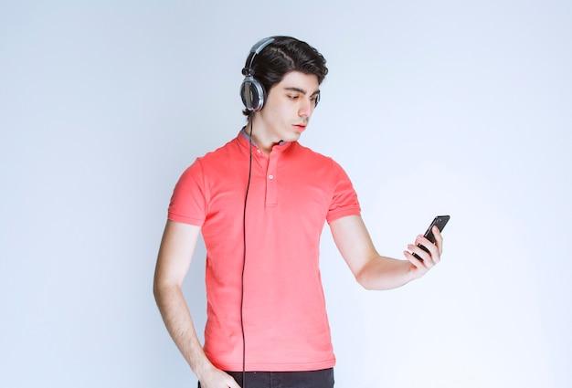 Uomo con le cuffie che imposta musica o effettua una chiamata in linea.