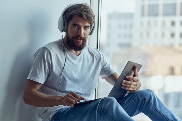 창턱 기술에 앉아 헤드폰을 가진 남자