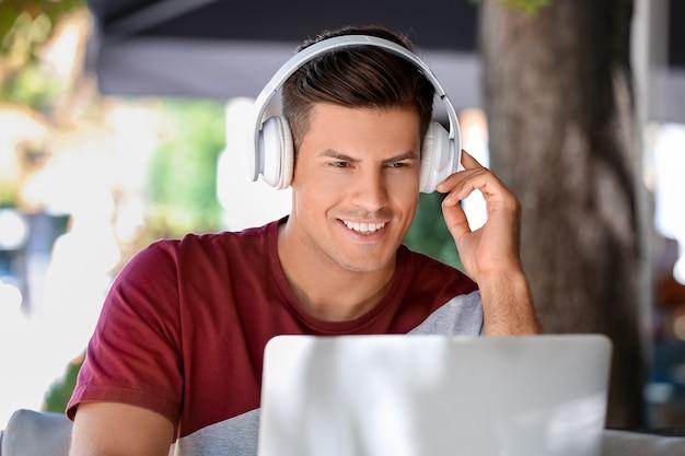 屋外カフェでラップトップに取り組んでいるヘッドフォンを持つ男