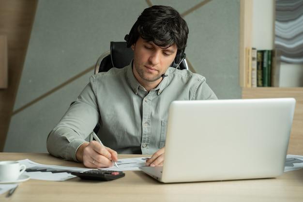 Человек с гарнитурой и портативным компьютером, имеющим видеоконференцию в офисе мужчина на рабочем месте, разговаривает и жестикулирует, проводит видеоконференцию